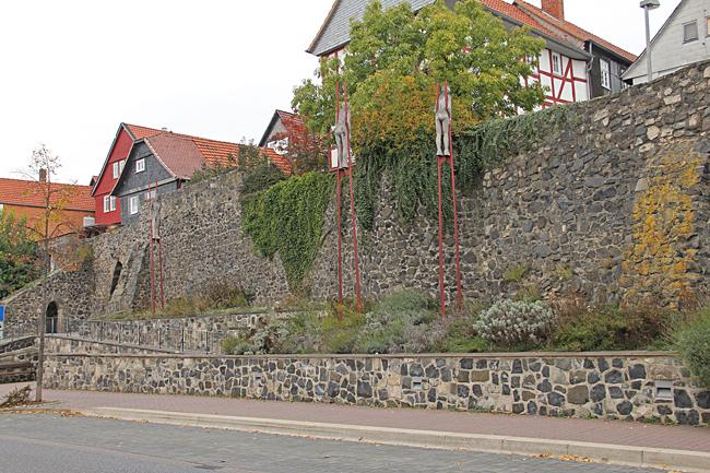 Gubbar på styltor kikar in över stadens mur.