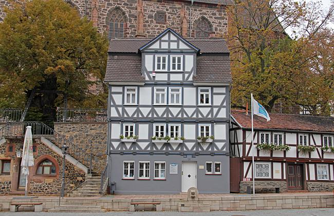 Ett litet fint korsvirkeshus med den ståtliga kyrkan som fondvägg.