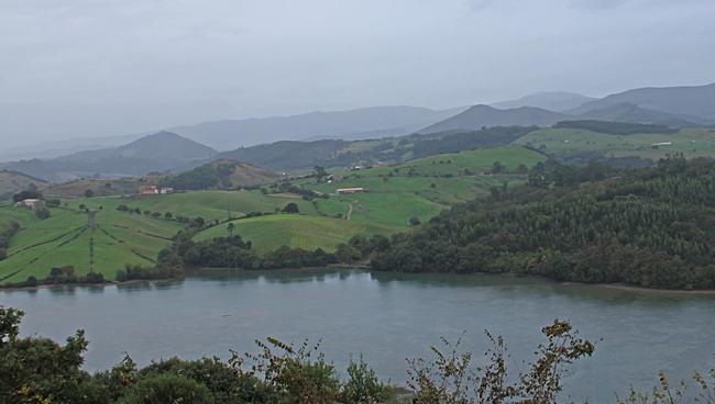 Lanskapet med gröna kullar och berg i bakgrunden.