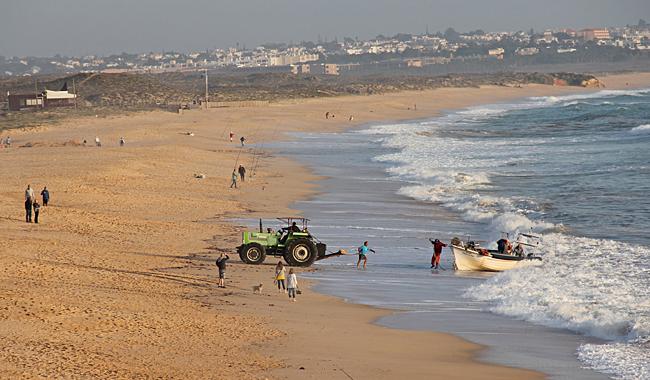 När fiskebåtarna kommer in kör de med full fart upp på stranden där en traktor möter upp för bogsering sista biten.