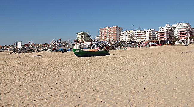 Fiskarnas båtar uppdragna på stranden framför hotellkomplexen.