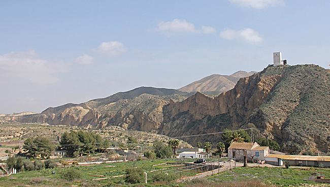På bilden syns det karga landskapet med höga berg som finns runt staden. Högst uppe på berget syns El castillo de Huércal-Overa med sitt moderna arkitektritade torn.