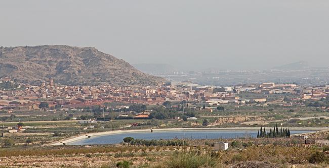 Utsikt över Agost med vattendamm i förgrunden.