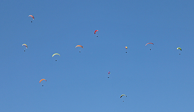 Ett gäng skärmflygare skymtar över en bergstopp.