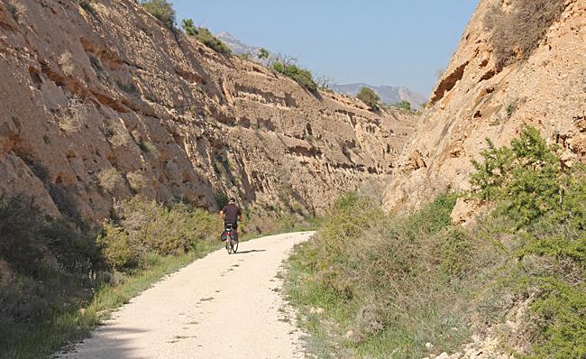 Vägen går genom djupa skärningar i leriga kullar.
