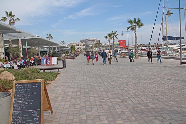 Den breda strandpromenaden mitt emot hamnen kantas av många restauranger.