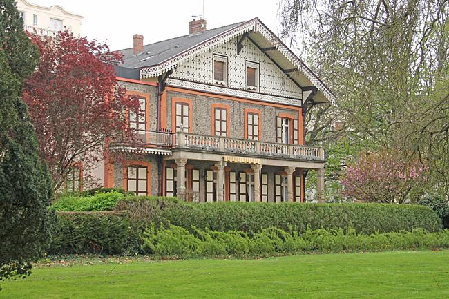 Ett charmigt hus skymtar mellan grönskan i parken som löper längs floden.