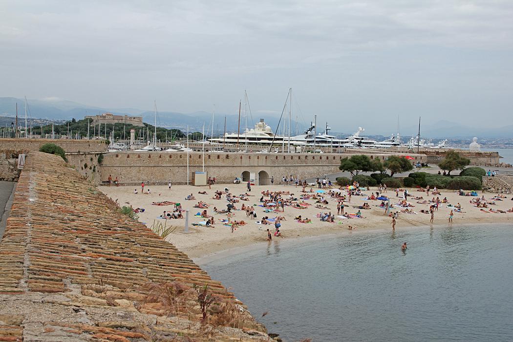 Liten badstrand med hamnen för lyxbåtar i bakgrunden.