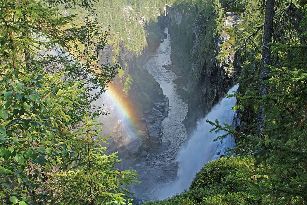 Vid solsken bryts ljuset till en regnbåge när vattnet störtar ner i ravinen.